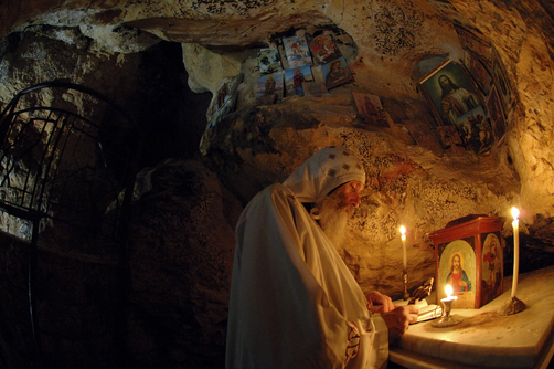 Coptic monk praying in original cave of St. Anthony.